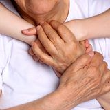 Farmor- och sondotterhållhänder med stor förälskelse arkivbild