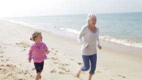 Farmor- och sondotterspring längs stranden tillsammans stock video
