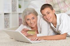 Farmor och sonson som använder bärbara datorn, online-shoppingbegrepp Arkivbild