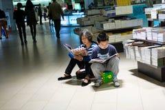 Farmor- och sonsonläsning i bokhandeln Royaltyfri Fotografi