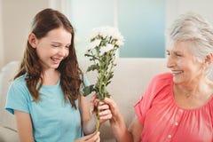 Farmor som ger en grupp av blommor till hennes sondotter Arkivbilder
