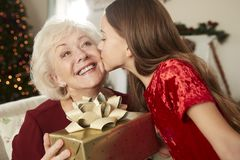 Farmor som hemma mottar julgåvan från sondotter arkivfoton