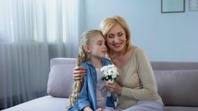 Farmor som kramar sondottern och tillsammans uppskattar hennes gåva, tid royaltyfri bild