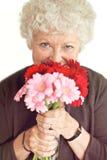 Farmor som luktar blommorna Royaltyfri Foto