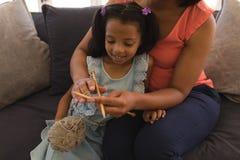 Farmor som undervisar hennes sondotter hur till knitt i vardagsrum arkivbilder