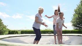 Farmor, sondotter och moder som studsar på trampolinen lager videofilmer