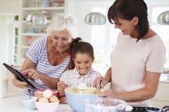Farmor-, sondotter- och moderbakningkaka i kök arkivbild