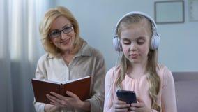 Farmorläsebok och se ungen som lyssnar till talboken i hörlurar lager videofilmer
