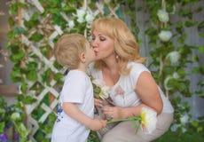 Farmorsonson, både blonda kyssar, kel och kyssa royaltyfria bilder