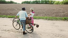 Farms on a bicycle with baskets are on the road. stock video footage