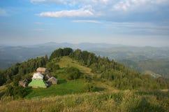 Farmstead на зеленом наклоне в Carpatians стоковая фотография rf