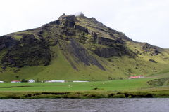 Farmstead Near a Mountain in Iceland. A farm is nestled against a mountainside in Iceland Royalty Free Stock Images