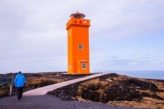 Faro anaranjado con el ser humano en el primero plano foto de archivo