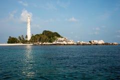 Faro bianco che sta sulla spiaggia dell'isola con le rocce nell'isola del Belitung, Indonesia Fotografia Stock Libera da Diritti