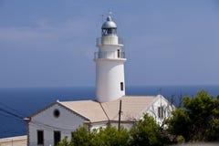 Faro bianco sulle rocce negli azzurri dell'acqua dell'oceano del mare Immagini Stock Libere da Diritti