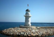 Faro blanco cerca de la costa con un indicador rojo Fotos de archivo libres de regalías
