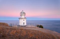 Faro blanco hermoso en la costa costa del océano en la puesta del sol Paisaje imagenes de archivo
