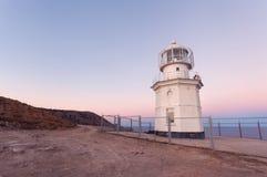 Faro blanco hermoso en la costa costa del océano en la puesta del sol Paisaje fotografía de archivo libre de regalías