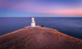 Faro blanco hermoso en la costa costa del océano en la puesta del sol Paisaje fotos de archivo