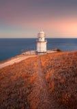 Faro blanco hermoso en la costa costa del océano en la puesta del sol Paisaje imagen de archivo libre de regalías