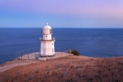 Faro blanco hermoso en la costa costa del océano en la puesta del sol Paisaje imagen de archivo