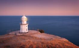 Faro blanco hermoso en la costa costa del océano en la puesta del sol Paisaje imágenes de archivo libres de regalías