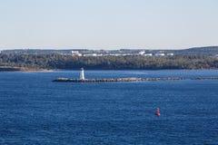 Faro blanco y marcador rojo en agua azul Imágenes de archivo libres de regalías