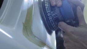 Faro che lucida, elaborazione delle luci dell'automobile Un lavoratore di servizio dell'automobile lucida il faro di una carrozza video d archivio