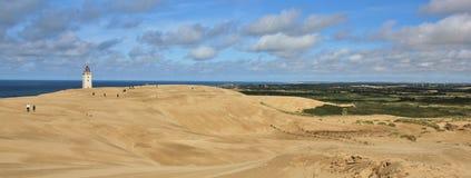 Faro che scompare lentamente sotto una grande duna di sabbia Mare blu a Fotografie Stock Libere da Diritti