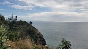 Faro con el embarcadero en horizonte Fotografía de archivo