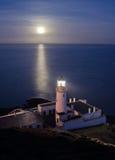 Faro con la luna piena che riflette nel mare Fotografia Stock
