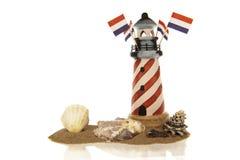 Faro con las banderas y las cáscaras en arena Imágenes de archivo libres de regalías