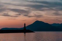 Faro Contro il contesto delle montagne immagini stock