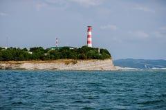 Faro dal mare sulle rocce un il giorno soleggiato di estate Fotografie Stock Libere da Diritti