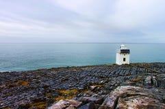 Faro de Burren en la costa rocosa de Irlanda. Foto de archivo