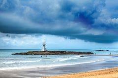 Faro debajo de las nubes de tormenta sobre el mar Foto de archivo