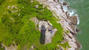 Faro del mar de la visión superior en la isla rocosa en el mar azul Casa ligera del paisaje aéreo en orilla verde en el océano metrajes