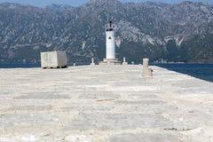 Faro del mar en la isla del Gospa-od-Shkrpjela en la bahía de Kotor imagenes de archivo