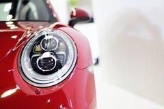 Faro del primo piano del fondo rosso dell'automobile sportiva Fotografia Stock