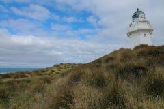 Faro del punto di Waipapa con le dune ed il cielo nuvoloso fotografia stock