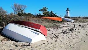Faro della Nuova Inghilterra con i pescherecci variopinti sulla riva fotografie stock libere da diritti