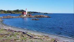 Faro di Fisgard con le onde lungo la costa del Pacifico vicino a Victoria, BC, il Canada stock footage