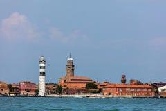 Faro di Murano Lighthouse and Murano island. MURANO, ITALY - APRIL 30 2016: Faro di Murano Lighthouse on the Venetian island of Murano, a round cylindrical stone royalty free stock photo