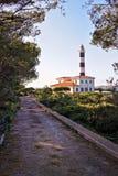 Faro di Portocolom con il passaggio pedonale che conduce attraverso il giardino in pieno degli alberi, Mallorca, spagna immagini stock