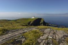 Faro di Stoer sulle scogliere irregolari con cielo blu splendido nei precedenti Punto di Stoer, altopiani, Scozia, Gran Bretagna fotografia stock libera da diritti