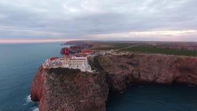 Faro e scogliere di vista aerea a capo St Vincent al tramonto Sagres, Algarve, Portogallo video d archivio