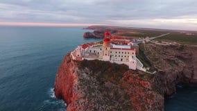 Faro e scogliere di vista aerea a capo St Vincent al tramonto Sagres, Algarve, Portogallo stock footage