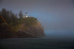 Faro en el acantilado sobre el océano tranquilo brumoso Imagenes de archivo