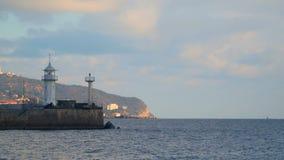 Faro en el embarcadero en el fondo de montañas almacen de video
