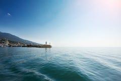 Faro en el fondo de montañas y del cielo azul imagenes de archivo